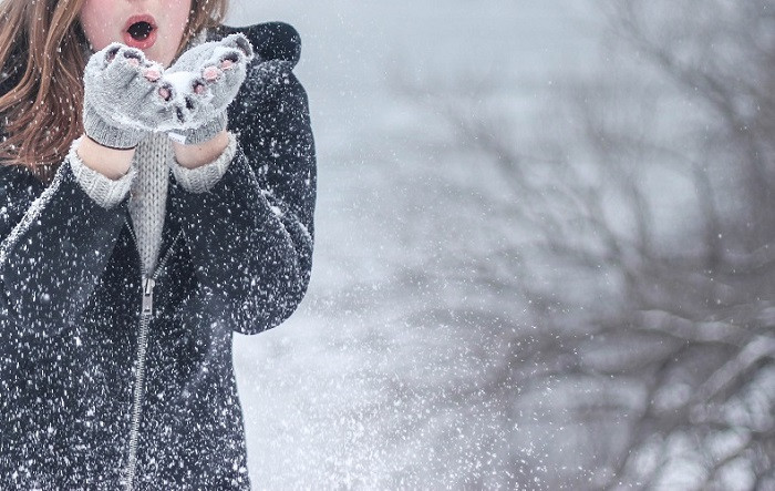women with brown hair and light pink lips, wearing grey jacket and white fingerless gloves, blows the snowflakes.