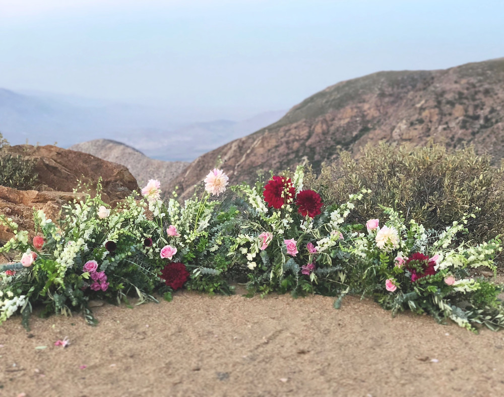 Half moon growing flower arch filled with pops of bright colored dahlias over looking the rolling hills for an elopement at Kwaaymii Point in Julian, CA by San Diego Wedding Florist Le Champange Projects