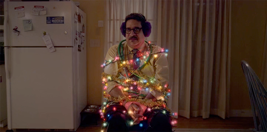 A man is tied to a chair with Christmas tree lights