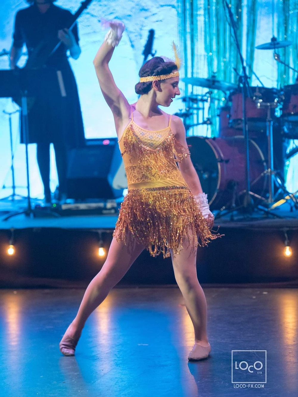 A dancer in a yellow fringe flapper dress and feather headband on stage with a band set up behind her.