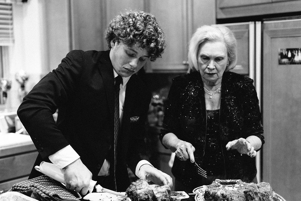 Grandmother and grandson carving up a Christmas ham