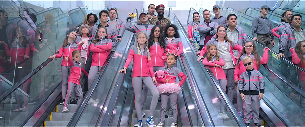 Feel the Beat movie still showing three escalators filled with adults and kids wearing pink and grey uniforms.