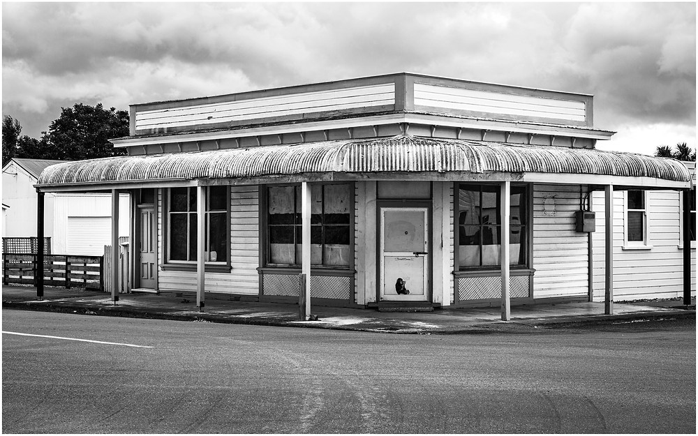 Stormy skies gather over an abandoned New Zealand corner store building
