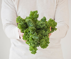 Close up image of a person holding a bunch of green ruffly Kale.