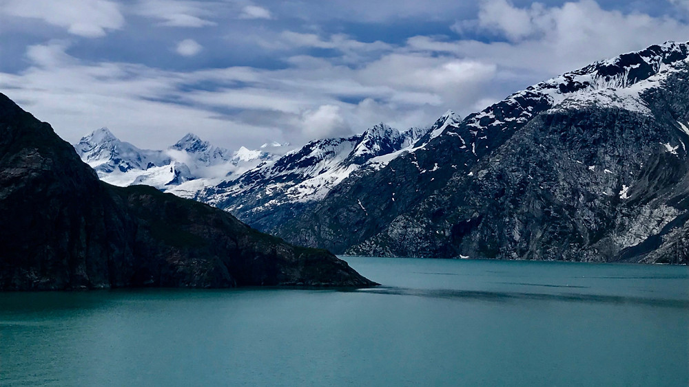 Blue waters and snow capped mountains of Glacier Bay, Alaska