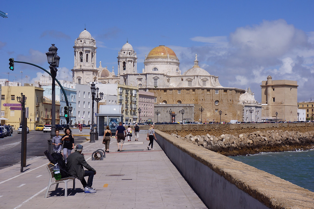 Sea wall promenade with Cádiz cathedral in the background.