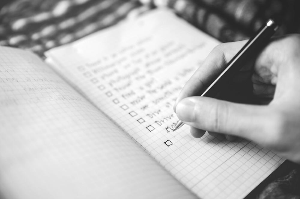 mao escrevendo em um caderno, caneta preta
