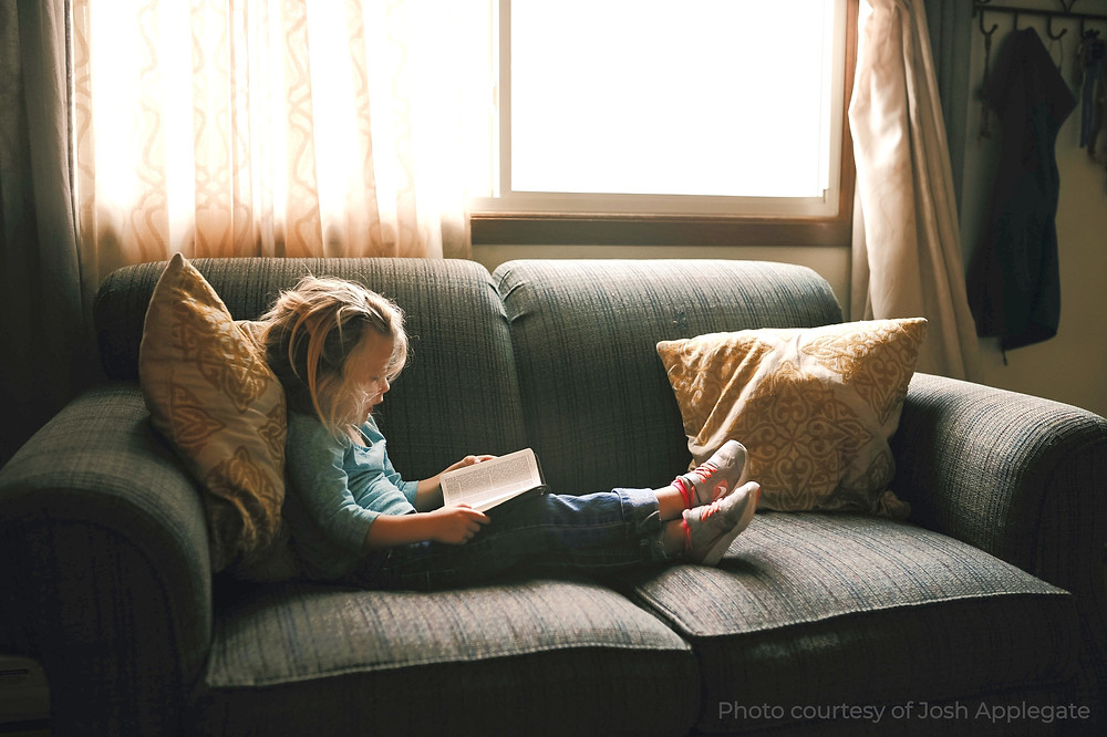 A dyslexic girl sits on the couch reading a book written specifically for struggling readers