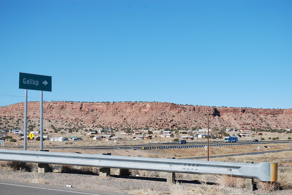 Vivid blue sky, overlooking a highway  near the town of Gallup, New Mexico, in desert countryside next to a large rock cliff.