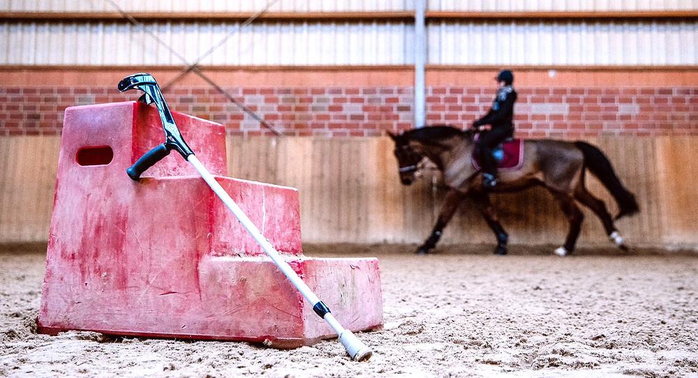 In der Reithalle. Im Vordergrund eine dreistufige Aufstieghilfe an der eine Krücke lehnt. Im Hintergrund eine Reiterin mit ihrem Pferd im Galopp.