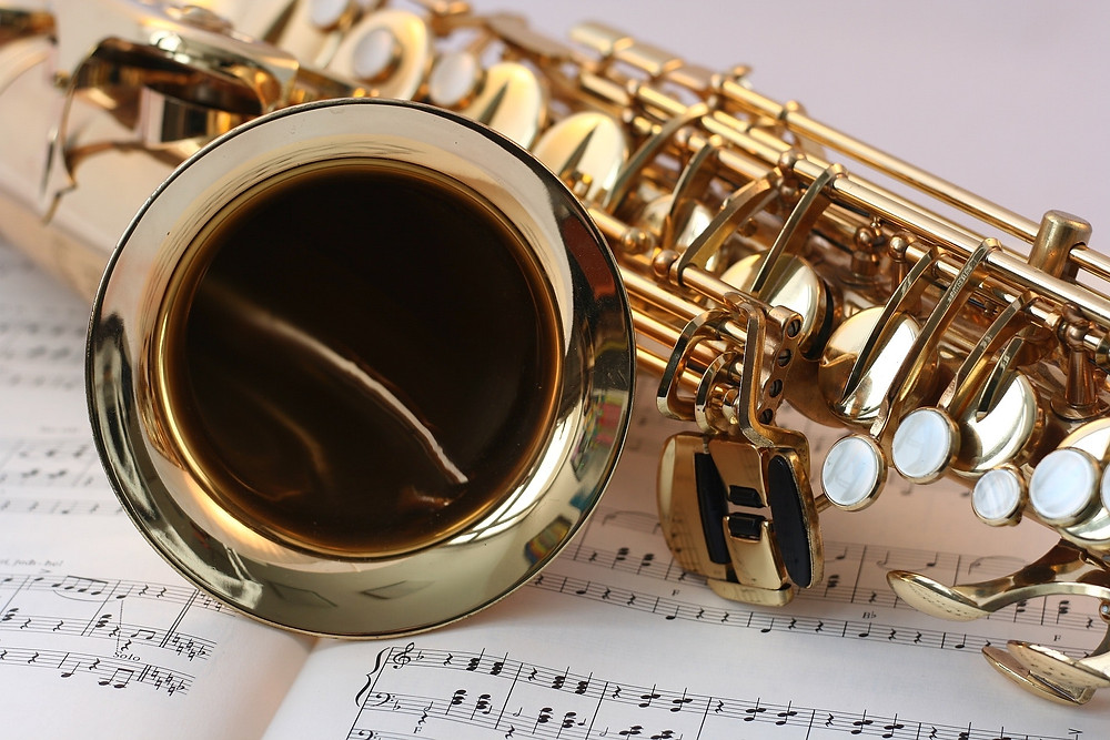 A shiny saxophone with mother-of-pearl keys is laying on sheet music