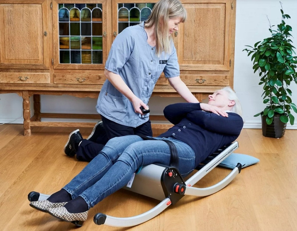 A carer using the Raizer lifting chair to get a fallen lady back to a seated position.