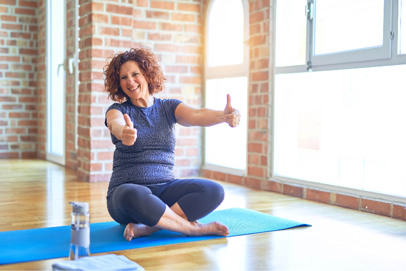 Woman in yoga studio giving a thumbs-up