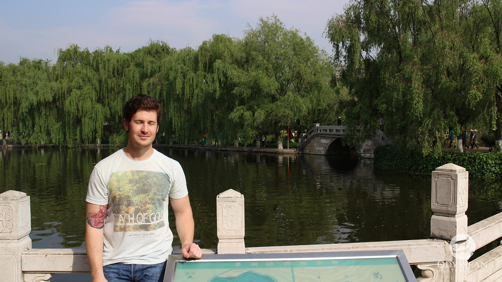 Man visiting Kunming's Green Lake in China, eyes closed for a travel photo