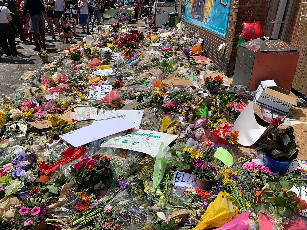 Image: Flowers at the George Floyd Memorial. Photo Credit: Cirien Saadeh