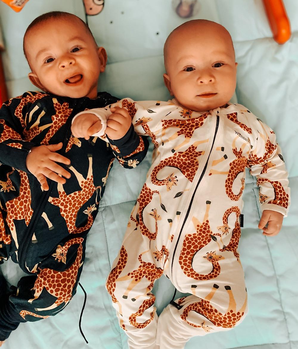 twin babies wearing blue and white giraffe print Bonds Wondersuits