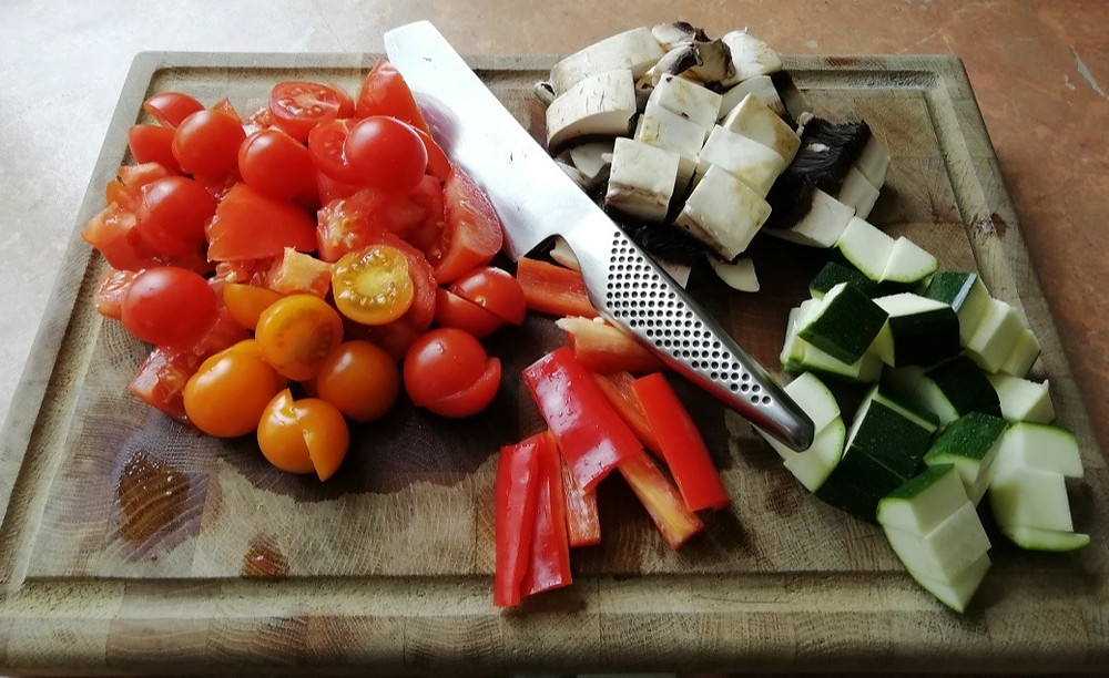 A chopping board with fress vegetables chopped up in readiness for a plant based diet.