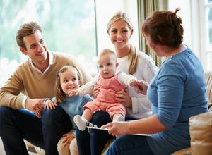 Дадилката седи со родителите и разговара во присуство на двете деца