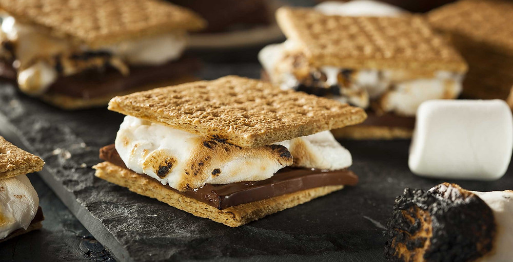 Close view of a warm s'more with grahams, milk chocolate, and a toasted marshmallow with toasted edges.