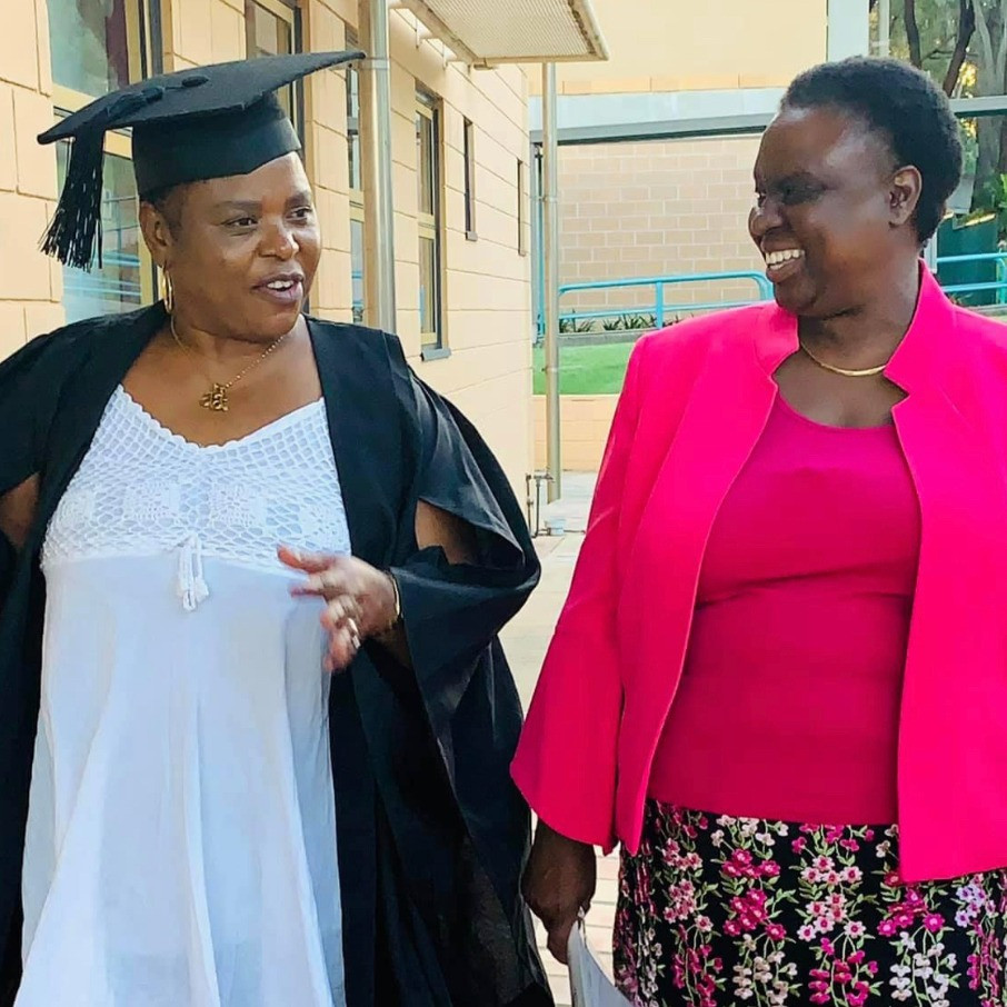 One woman in her graduation cloak and hat speaks with another woman as they walk along a path.