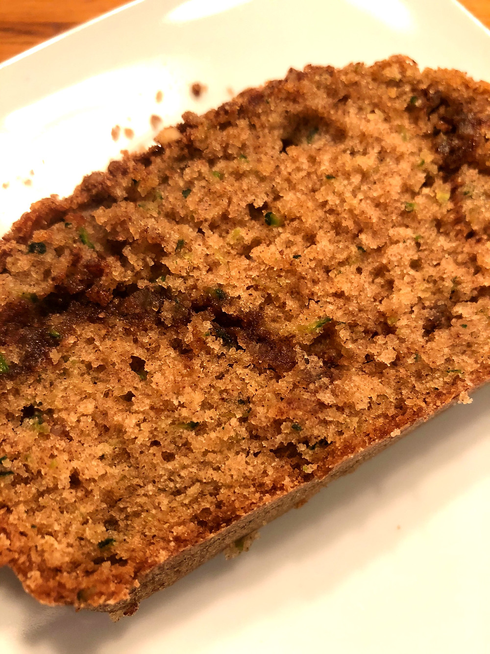 A close up of a slice of bread that has specks of spice and sugar as well as small slivers of green zucchini.