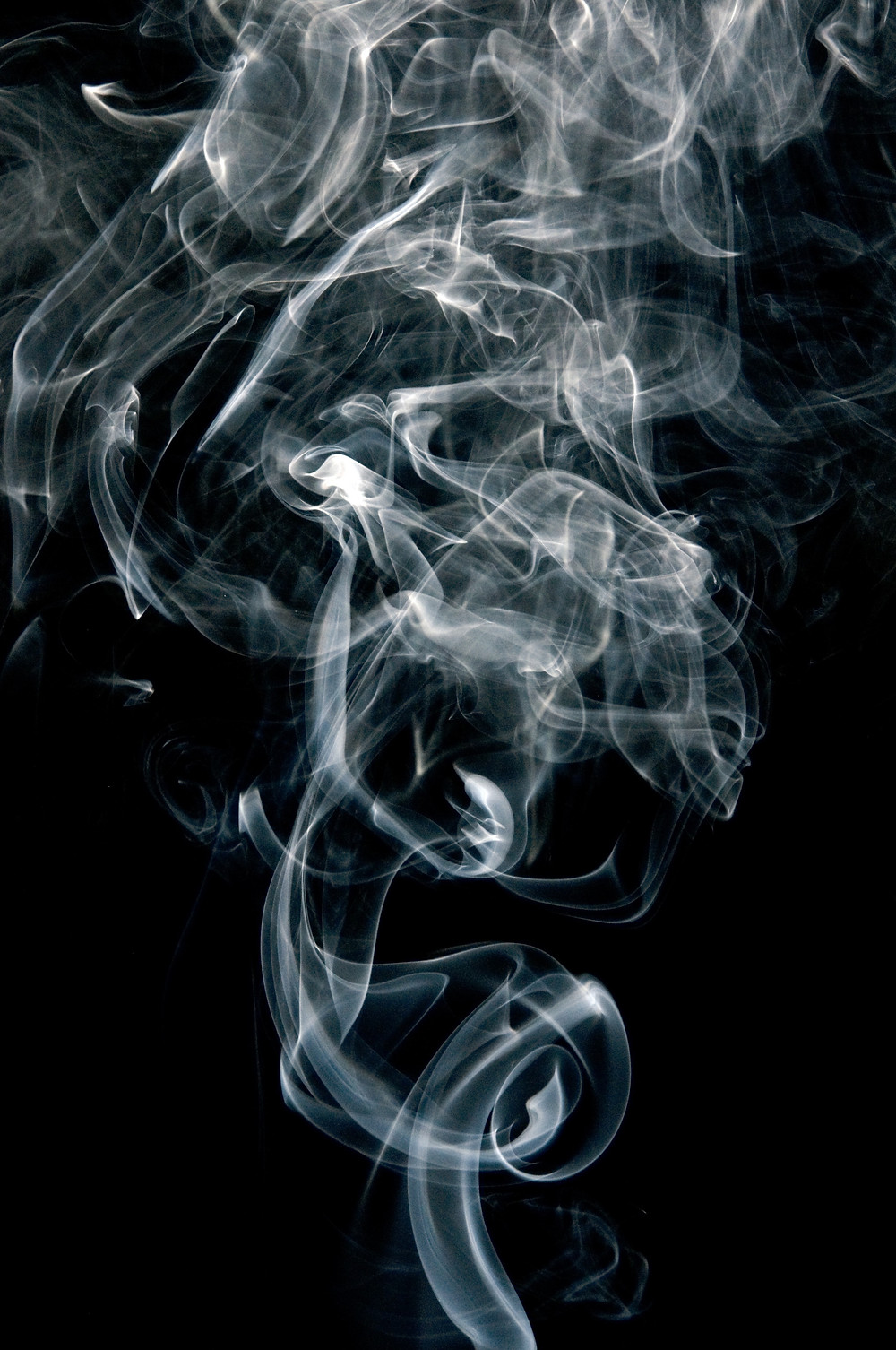 Smoke dissipates on a black background.