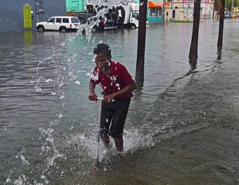 A young boy makes like the S-Team and navigate Miami's water-soaked street.