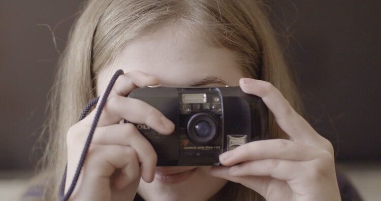 Noah, a teenage girl, holds a point and click camera up to her face and looks through the lens, pointing it straight at you.