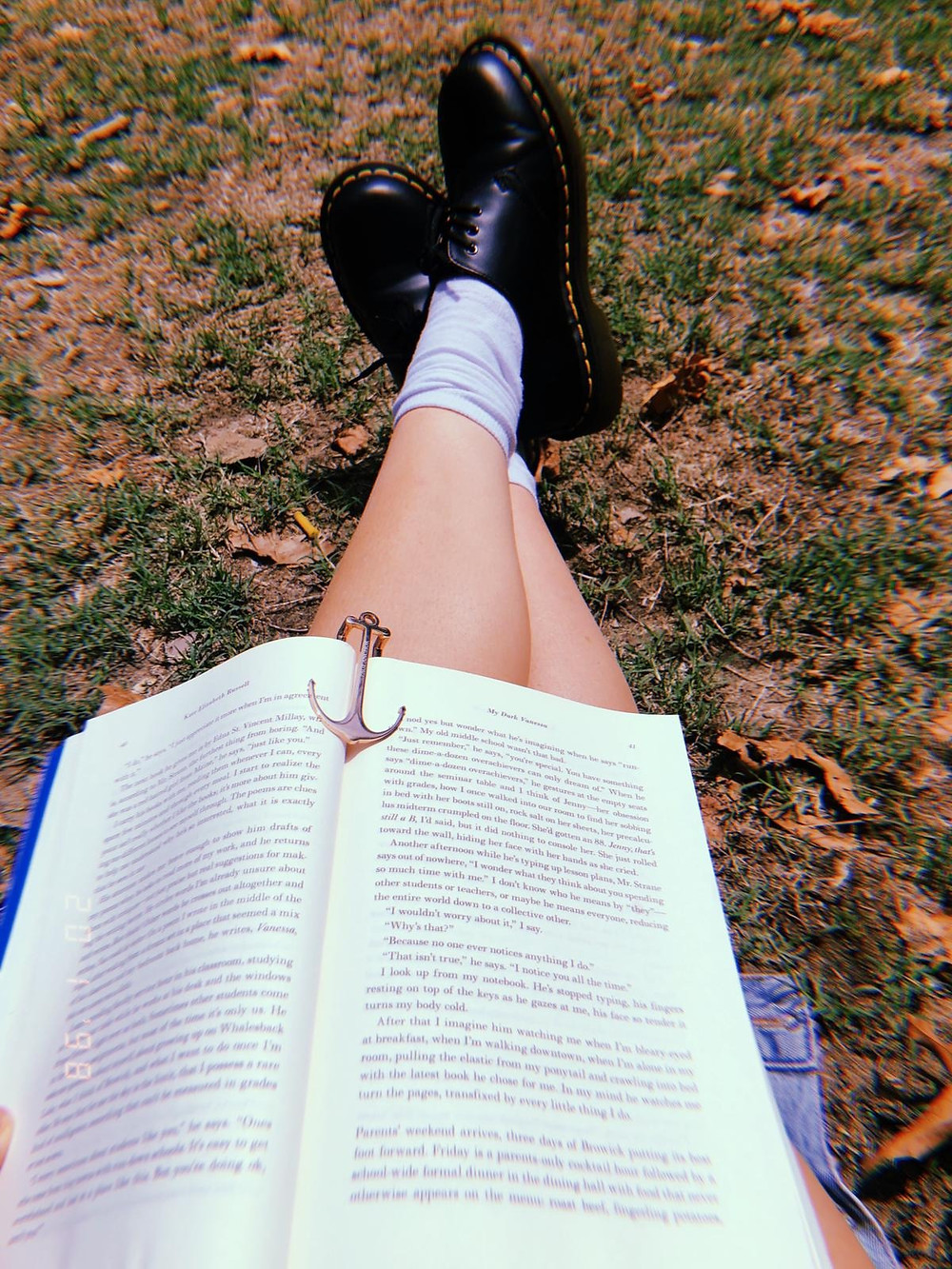 Open copy of My Dark Vanessa on the lap of someone sitting on a sunny lawn.