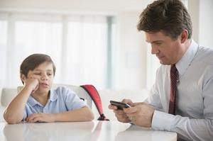 Таткото се занимава со својот мобилен телефон додека детето го гледа и се здодева