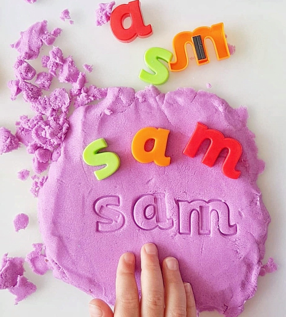 child learning names with kinetic sand