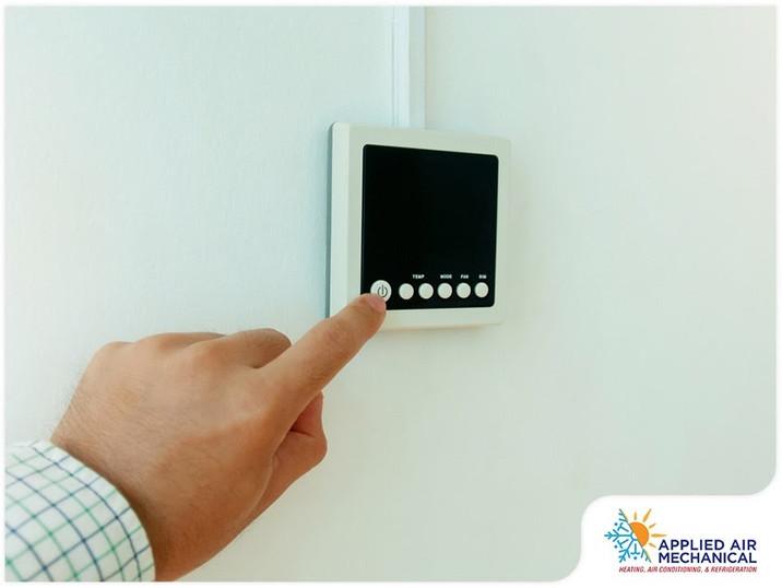 homeowner-adjusting-thermostat.jpg