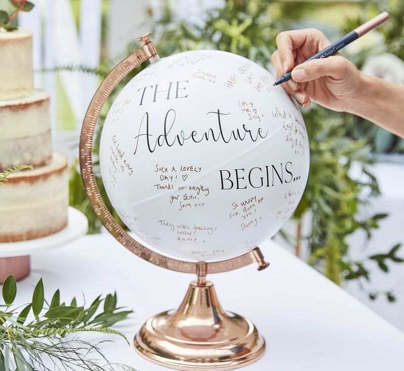 A white & gold globe, signed by wedding guests