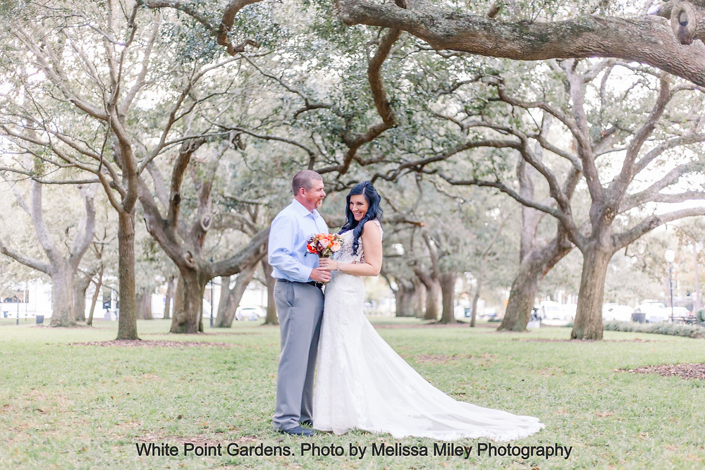 Bride and groom laugh under a canopy of trees at the Battery in Charleston, SC