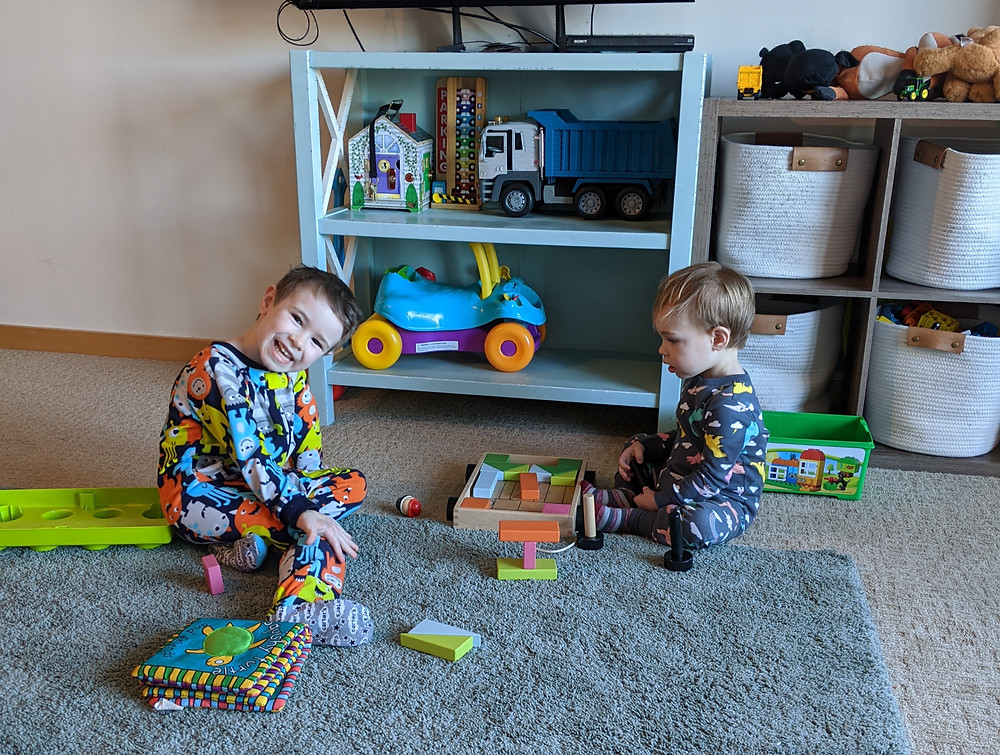 Two young boys in pajamas sit in a carpeted living room, playing with colorful blocks. Two shelves behind them hold more toys.