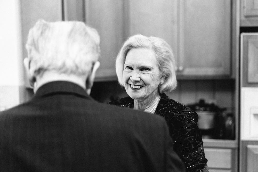 Hostess smiling at the camera over her husband's shoulder