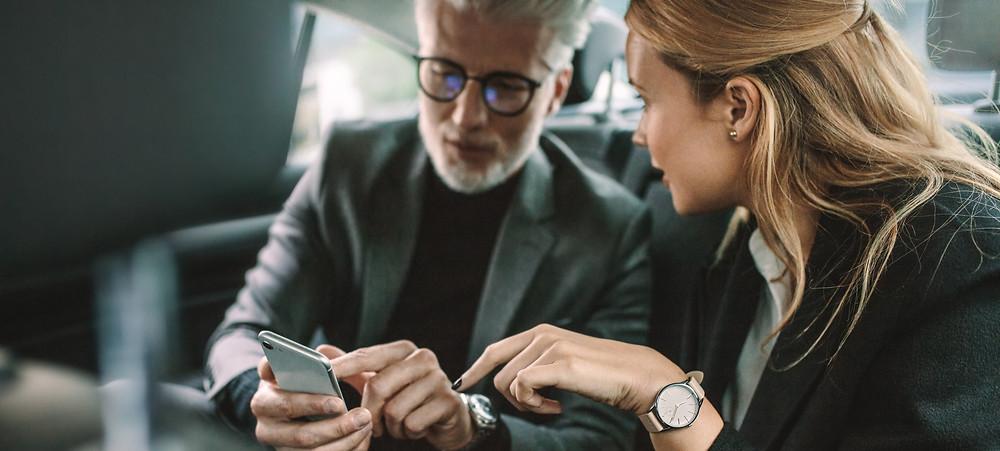 Mulher e homem em um carro olhando para celular