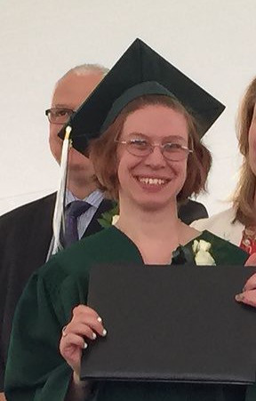 Image of Emily Webster, wearing her green graduation cap and gown, smiling as she holds her diploma.