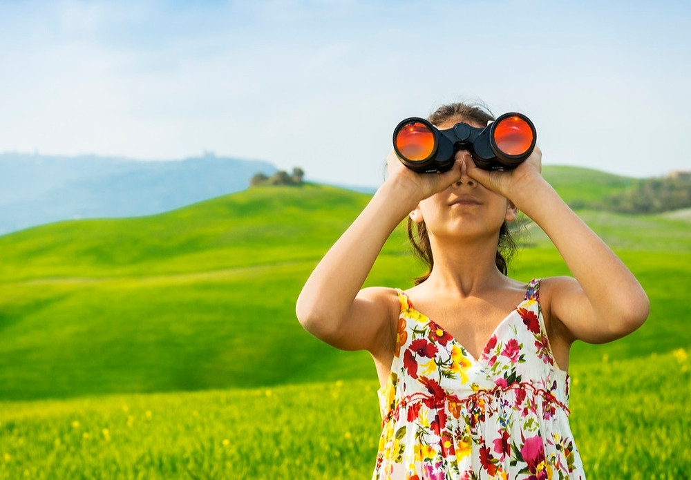 Woman in field using binoculars - How to find a copywriter in Dublin, Ireland