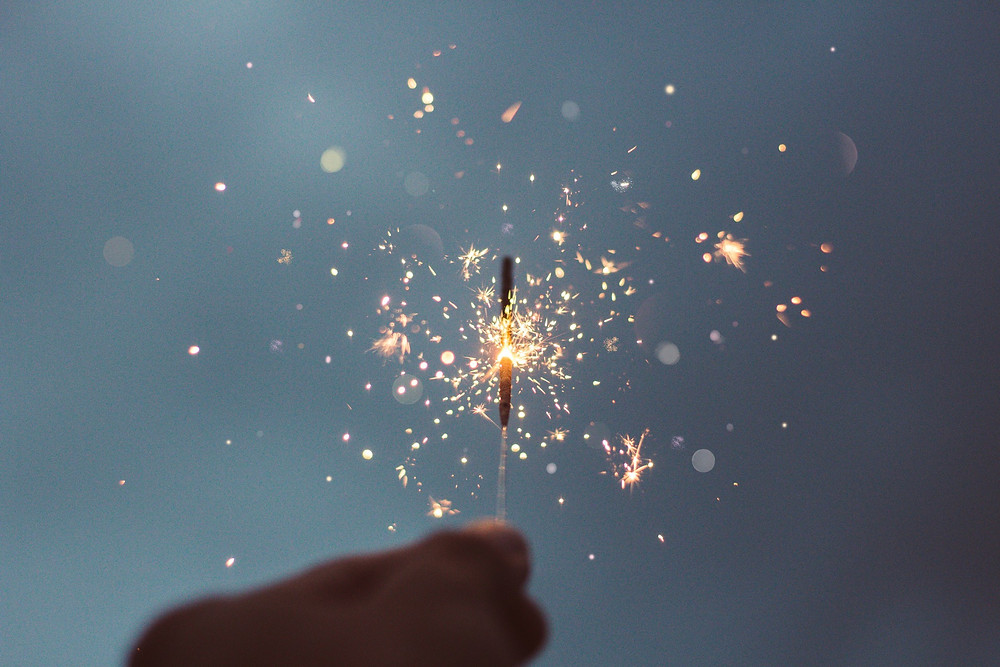 A close up image of a brightly lit sparkler against a twilight sky, Happy Fourth of July!
