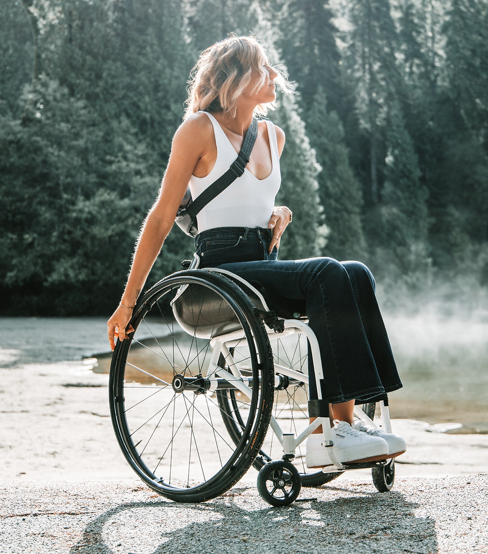 Young adult woman in a wheelchair. She has blonde hair and is wearing a white tank top and black long pants.