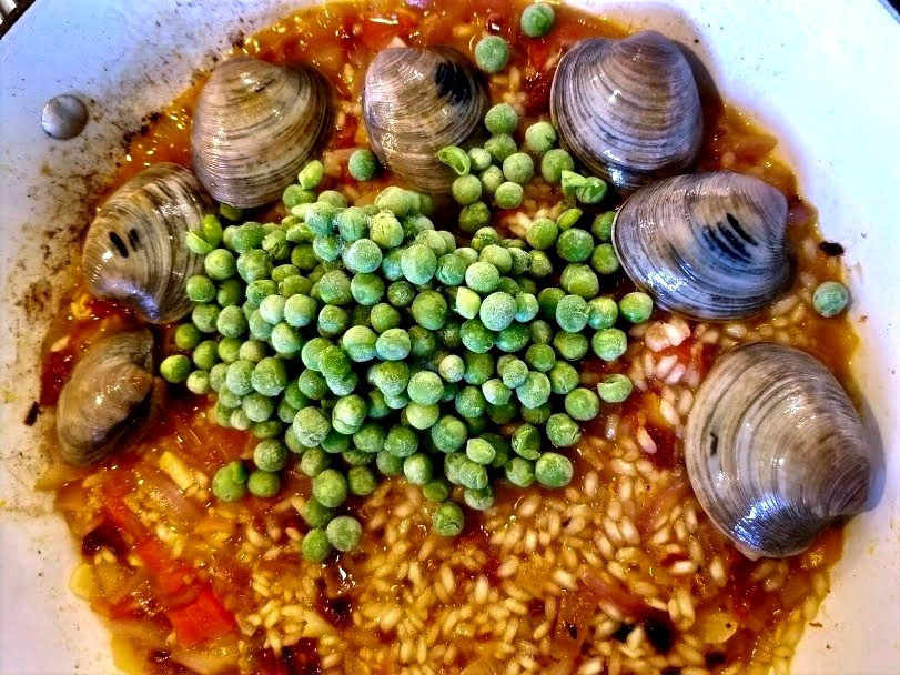 Paella cooking in a pan with clams and peas on top