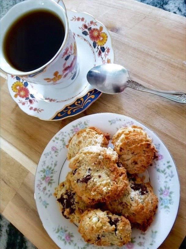 Plate of homemade coconut cookies with a cup of hot tea