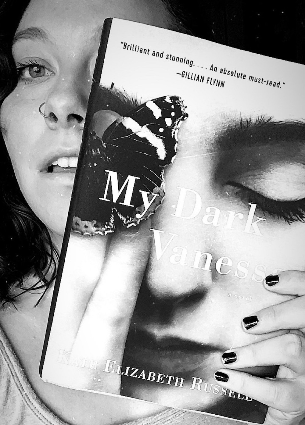 A woman, Maggie, holds up a copy of My Dark Vanessa to her face.