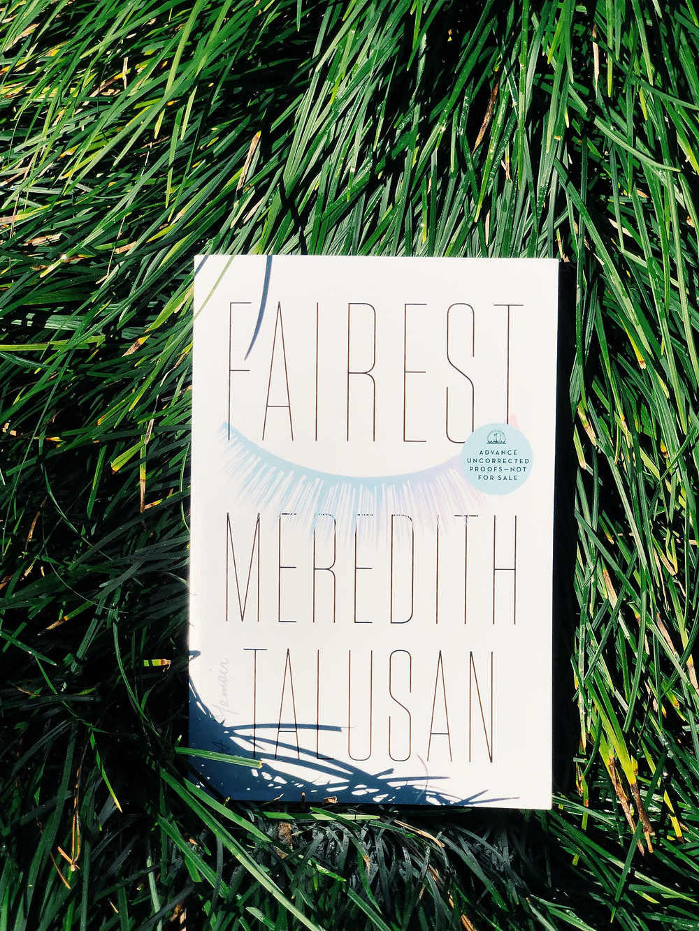 A copy of FAIREST lays in a bed of grass