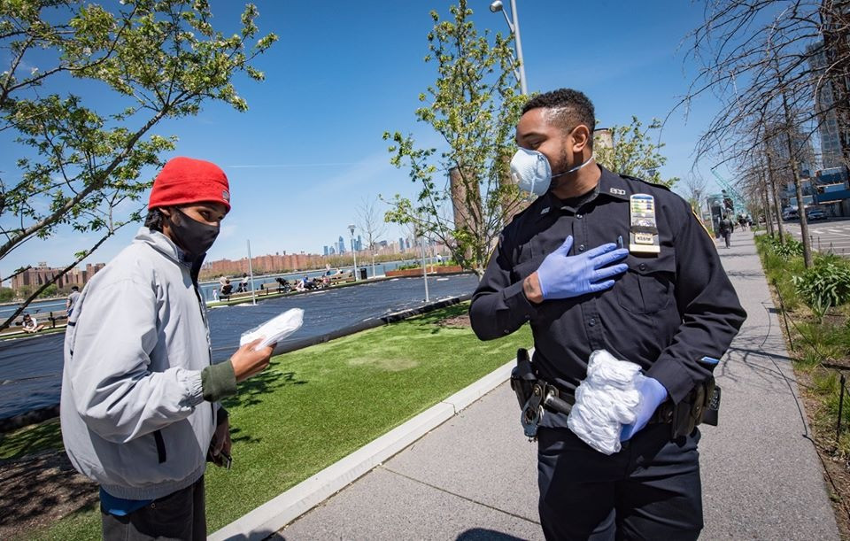 NYPD police officer handing out masks to public during COVID-19 pandemic