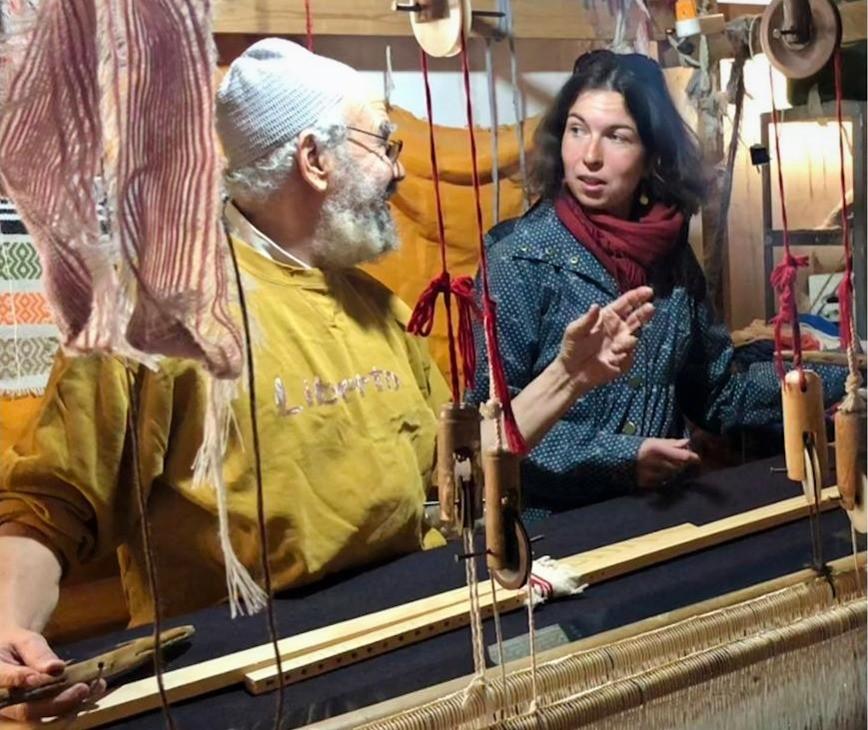 Starec ve zlute mikine a bile cepicce a vpravo Tereza Huclova, oba za tkalcovskym stavem