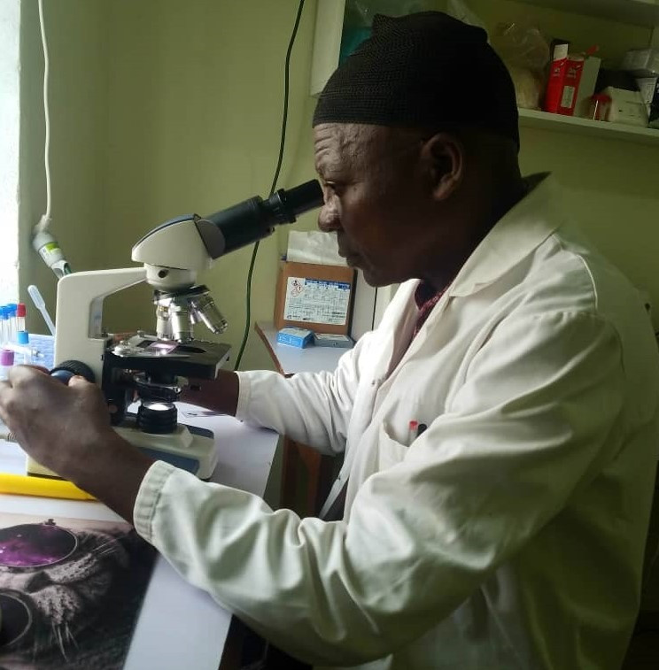 One of the Senior Laboratory Professionals at HELP HealthCare Services carrying out analysis on a microscope (Pa ASONGWE Mathias FON, former Head of Service at Mary of Africa Hospital Laboratory)
