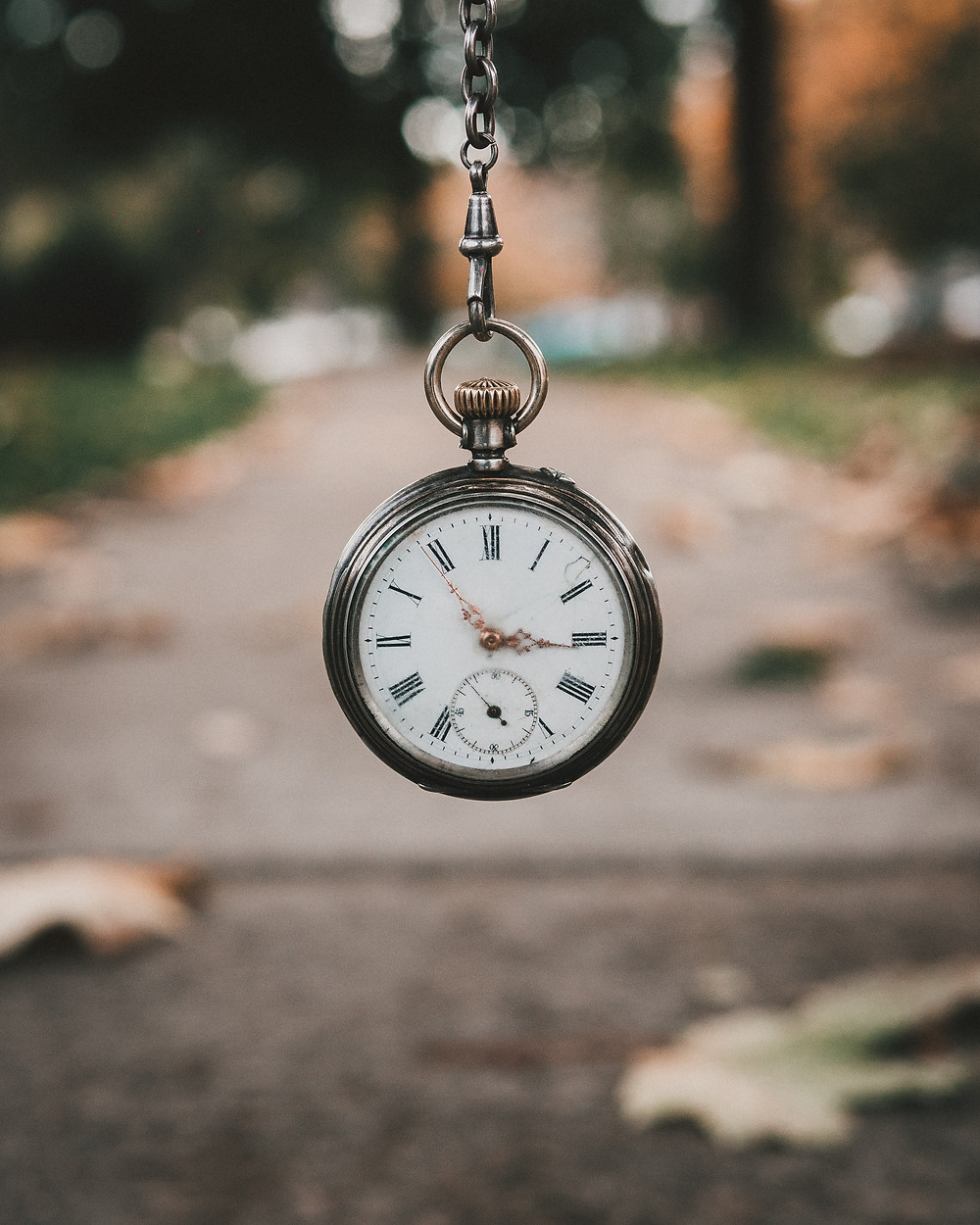 Antique stopwatch dangling in front of a leaf covered sidewalk signifying how long EMDR treatment takes for trauma treatment in Denver CO. Our caring and experienced therapists provide EMDR for trauma counseling at Catalyss Counseling in Englewood CO 80209 and 80210