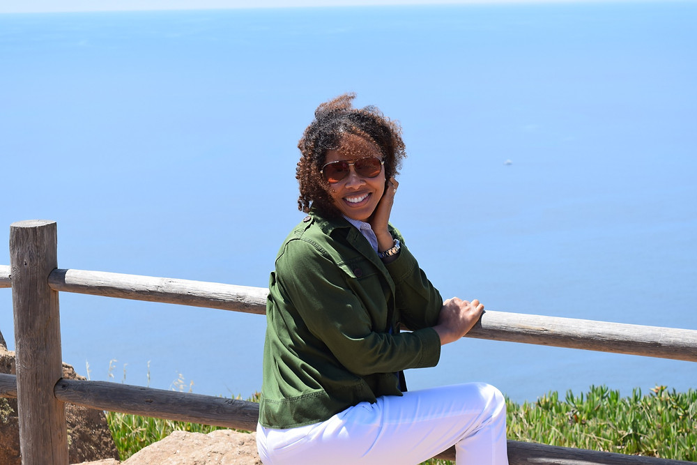 Lauren Francis-Sharma , the author, sits on an overlook of ocean, looking at camera and holding her hair back from the wind